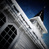 Small local white clapboard church in winter with icicles hanging from the roof under a blue winter sky