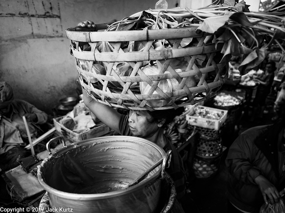 07 AUGUST 2017 - BEBANDEM, BALI, INDONESIA: A woman leaves the market in Bebandem, in far eastern Bali, at the end of her work day. The market is known for baskets, which are woven in the area. Bali's local markets are open on an every three day rotating schedule because venders travel from town to town. Before modern refrigeration and convenience stores became common place on Bali, markets were thriving community gatherings. Fewer people shop at markets now as more and more consumers go to convenience stores and more families have refrigerators.     PHOTO BY JACK KURTZ
