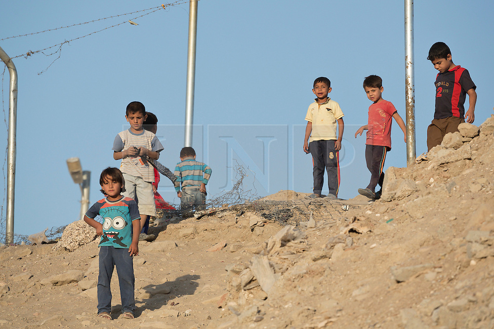 Licensed to London News Pictures. 22/10/2016. Young Iraqi refugees  stand around a broken fence at the Dibaga refugee camp near Makhmur, Iraq.<br />