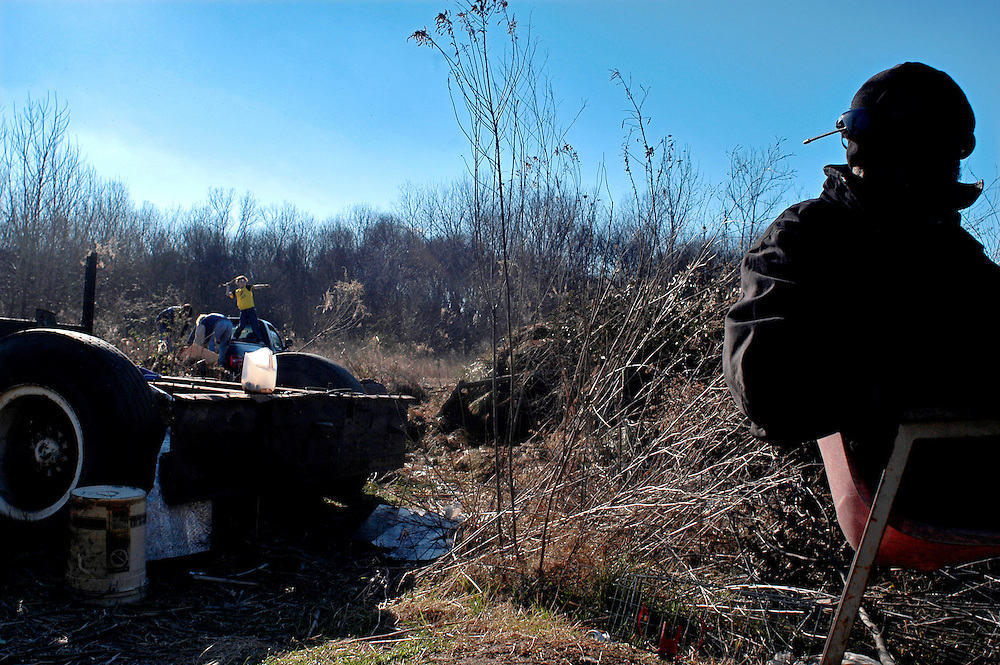 Pearlie, right, sits in a chair drinking coffee while Robert Mancil, 11, in yellow, tosses a peice of pulp wood onto a pile with the help of his sister Ashley Mancil, 14, and mother Gina Mancil, both bent over picking up wood from the back of a truck, Tuesday January 27, 2003. The Mancils bring pulp wood from downed trees to Pearlie on a regular basis. Pearlie uses the wood for heat and cooking. (photo by Matt Roth)