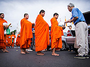 "21 JULY 2013 - BANGKOK, THAILAND:  A man gives monks at Wat Benchamabophit food and alms on the first day of Vassa, the three-month annual retreat observed by Theravada monks and nuns. On the first day of Vassa (or Buddhist Lent) many Buddhists visit their temples to ""make merit."" During Vassa, monks and nuns remain inside monasteries and temple grounds, devoting their time to intensive meditation and study. Laypeople support the monastic sangha by bringing food, candles and other offerings to temples. Laypeople also often observe Vassa by giving up something, such as smoking or eating meat. For this reason, westerners sometimes call Vassa the ""Buddhist Lent.""       PHOTO BY JACK KURTZ"