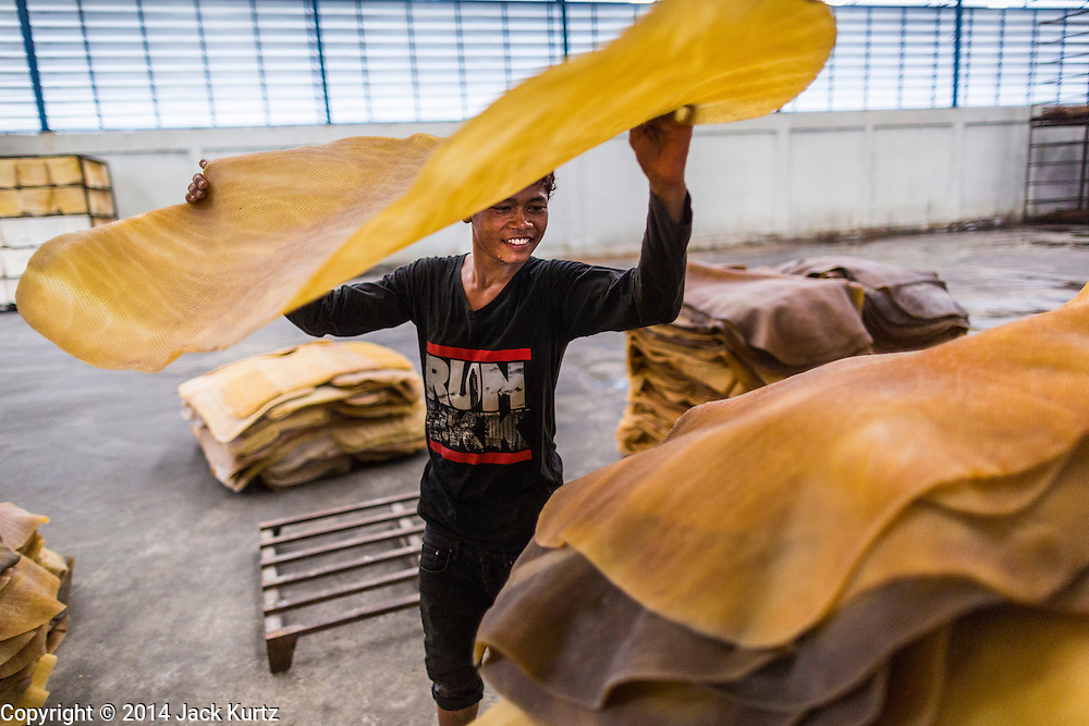 02 SEPTEMBER 2014 - BO THONG, CHONBURI, THAILAND: Workers at Bothong Rubber Fund Cooperative in Bo Thong, Chonburi, Thailand, unload rubber sheets from a farmer's pickup truck. Thailand is the leading rubber exporter in the world. In the last two years, the price paid to rubber farmers has plunged from approximately 190 Baht per kilo (about $6.10 US) to 52 Baht per kilo (about $1.60 US). It costs about 65 Baht per kilo to produce rubber ($2.05 US). A rubber farmer in southern Thailand committed suicide over the weekend, allegedly because the low prices meant he couldn't provide for his family. Other rubber farmers have taken jobs in the construction trade or in Bangkok to provide for their families during the slump.    PHOTO BY JACK KURTZ