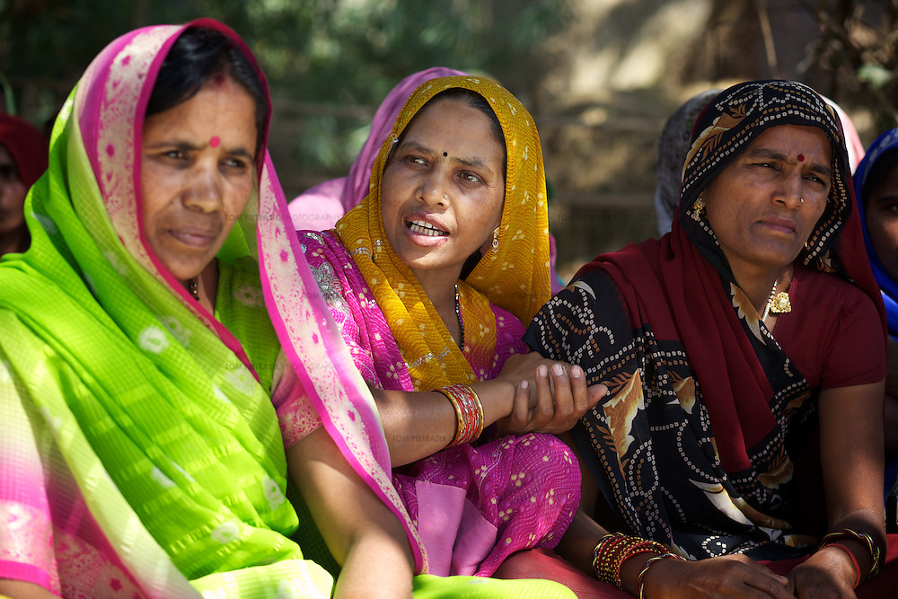 Shanti Devi (centre) and other women take part in the AROH Mahila Kisan Manch (Women farmers federation) monthly meeting in Deramunshi village. Among other ideas, the group plan a march on the issue of land reform. Such meetings allow issues like cultivation techniques, accessing good quality seeds, qualifying for subsidized inputs and training. <br /> <br /> Shanti Devi, 42, has one daughter and lives in Deramunshi village. She was domestically abused by her husband Jamna Prasada but without independent economic-means Shanti must continue to live in the same house as him although she refuses to cook for him. Shanti and Jamna used to own had one biga (1,300 sq metre) of land but he sold it. Though they also owned a shop, Shanti was furious. If she had joint ownership of the land, her husband would not have been able to sell it without her consent. She joined the AROH campaign because she thought her experience valuable for others. <br /> <br /> In the north Indian state of UP (Uttar Pradesh), women are responsible for 70 to 80 percent of agricultural work but their contribution remains neglected at all the levels: family, social, economic and policy. Over three quarters of UP's households are involved in farming of which 91% percent operate on land that is marginal and small. Small and marginal farmers often lack access to major agricultural services, such as credit, extension, insurance, and markets.<br /> <br /> On October 15, 2005 a movement called AROH was launched campaigning for the recognition of women as farmers. A federation of women farmers popularly known as &ldquo;Aroah Mahila Kissan Manch&rdquo; has been formed in all the districts of Uttar Pradesh. AROH has begun lobbying the UP government for women to be registered as joint owners - with their husbands - of land. At present only 6.5% of women own land in UP. AROH encourages women&rsquo;s co-operatives and other forms of group effort with the idea that these allow for the dissemination of information r
