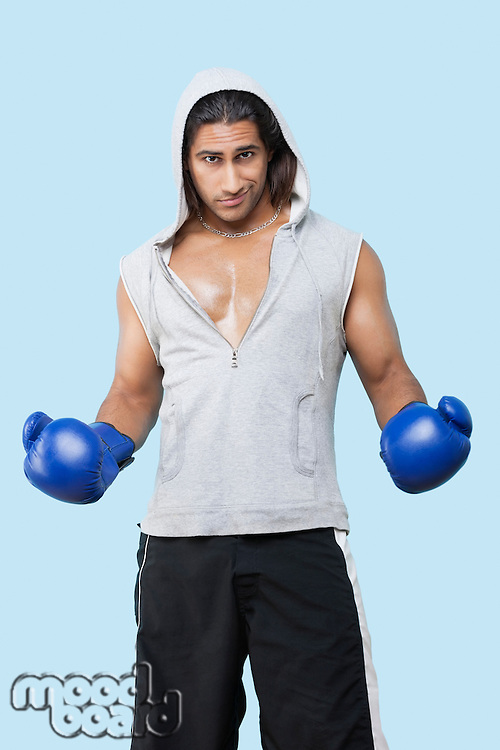 Portrait of a confident young man wearing boxing gloves standing over blue background