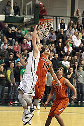 01 March 2014:  Dylan Overstreet puts up a shot ahead of a block by Caleb DeMoss during an NCAA mens division 3 CCIW  Championship basketball game between the Wheaton Thunder and the Illinois Wesleyan Titans in Shirk Center, Bloomington IL