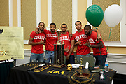 Alpha Phi Alpha fraternity poses with their booth.