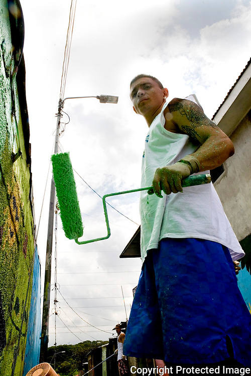Abraham painting a wall for a mural in La Carpio just days after be released from La Reforma.