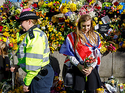© Licensed to London News Pictures. 25/03/2017. London, UK. Police officers and members of public pay their respects to the victims of Westminster terror attack outside the Houses of Parliament in London on 25 March 2017.  Photo credit: Tolga Akmen/LNP