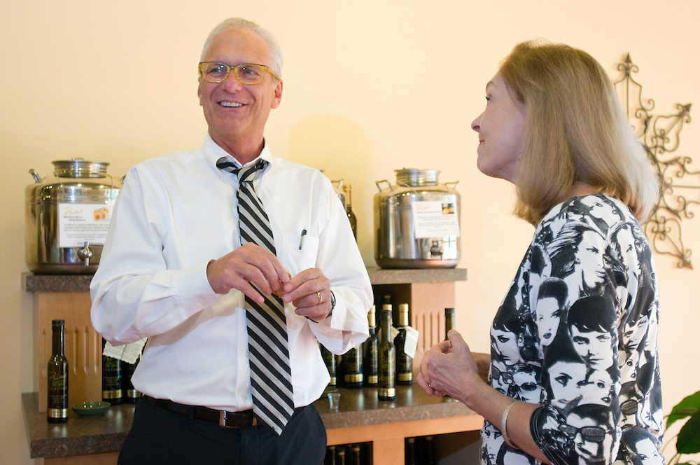 Carl Kuhl, left, talks with owner Beverly Bromley during a tasting event of flavored olive oils and traditional and white balsamic vinegars at Primo Oils and Vinegars in their store at 3628 Brownsboro Road,Tuesday, Aug. 21, 2012 in Louisville, Ky. (Photo by Brian Bohannon)