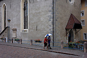 Elderly couple walk in the rain past the church in Klausen-Chiusa in the Italian south Tyrol.