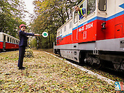 """The Childrens Railway <br /> <br /> In the outskirts of Budapest, through the scenic Buda hills, run a short, narrow-gauge railway line called Gyermekvasút, which is Hungarian for """"Children's Railway"""". But Gyermekvasút is not a toy train commonly found in amusement parks. It's a real railway line with real stations, real diesel locomotives pulling real coaches, and running on a real schedule. The """"Children"""" here are not the passengers. They are the railway workers.<br /> <br /> The Children's Railway is staffed and run mostly by pre-adolescent kids aged between 10 to 14, under adult supervision, of course. Only the driving and maintenance stuff are done by adults. All other jobs, from checking and issuing tickets, operating signals, making announcements and giving information to passengers, are performed by young people dressed in immaculate official uniforms complete with all the appropriate paraphernalia.<br /> The Children's Railway is a relic of the communist era, built at a time when the Young Pioneers movement was in full force. The Young Pioneers was a youth movement of the Communist Party, similar to the Scouts movement of the Western world, where young people learned skills of social cooperation and attended publicly funded summer camps. The early Young Pioneers were originally Scouts who took the Bolsheviks' side after the October Revolution of 1917. Many Scouts, however, resisted the communists and fought in the ranks of the White Army and interventionists against the Red Army during the Russian Civil War of 1917-1921. After communism got a firm hold over the country, the Scouting system was eradicated and replaced by the ideologically different Young Pioneer organization to properly educate children with Communist teachings.<br /> The Children's Railway, sometimes also called the Pioneer Railway, was a project of the Young Pioneers where teenagers and children learned the railway profession. They were established all across the Russian Union and Eastern """
