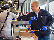 27 NOVEMBER 2019 - DES MOINES, IOWA: US Senator CORY BOOKER (D-NJ) bumps elbows with a client at Central Iowa Shelter and Services in Des Moines. They had to bump elbows rather than shake hands because Sen Booker was wearing gloves to handle food. Sen Booker helped plate up and serve lunch at the shelter. The shelter has about 180 beds and is full almost every night. In January and February, more than 250 people per night come to the shelter, which sets out overflow bedding. Senator Booker is running to be the Democratic nominee for the US Presidency in 2020. Iowa hosts the first selection event of the presidential election season. The Iowa caucuses are February 3, 2020.            PHOTO BY JACK KURTZ