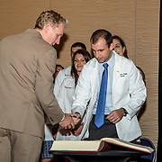 November 5, 2015, Baltimore, MD:<br /> Thomas Battey signs the book after receiving his coat during the University of Maryland Medical School Class of 2019 White Coat Ceremony at the Hilton Hotel in Baltimore, Maryland Thursday, November 5, 2015.<br /> (Photo by Billie Weiss)