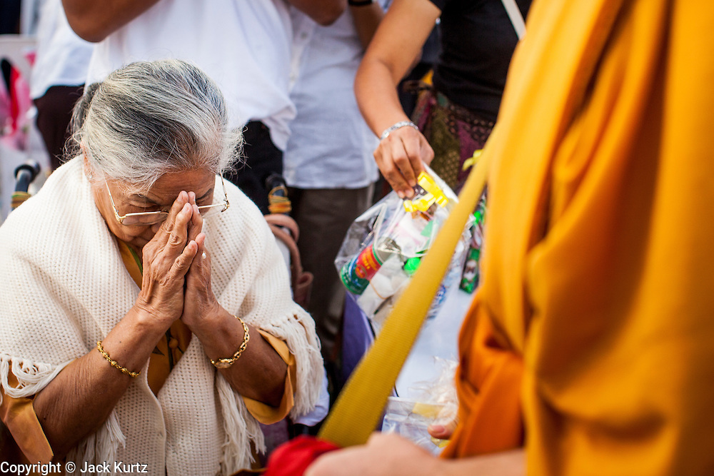 """01 JANUARY 2013 - BANGKOK, THAILAND:  A woman bows in respect after presenting a monk with an offering during a special merit making ceremony at Bangkok City Hall New Year's morning. Many Thais go to Buddhist temples and shrines to """"make merit"""" for the New Year. The traditional Thai New Year is based on the lunar calender and is celebrated in April, but the Gregorian New Year is celebrated throughout the Kingdom.     PHOTO BY JACK KURTZ"""