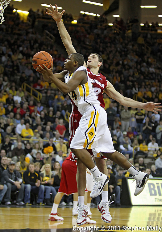 February 09 2011: Iowa Hawkeyes guard Bryce Cartwright (24) puts up a shot as Wisconsin Badgers forward Keaton Nankivil (52) defends during the second half of an NCAA college basketball game at Carver-Hawkeye Arena in Iowa City, Iowa on February 9, 2011. Wisconsin defeated Iowa 62-59.