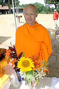 Buddhist monk standing by bouquet orange tiger lilies and a sunflower. Dragon Festival Lake Phalen Park St Paul Minnesota USA