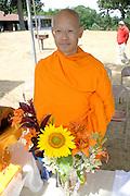 Buddhist monk standing by bouquet orange tiger lilies and a sunflower. Dragon Festival Lake Phalen Park St Paul Minnesota USA