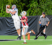 North Squad's Cully Curran, from Arlington High School, leaps to catch the ball over the hands of South Squad's Will Abbott, from Hopkinton High School, during the Shriner's All-Star Football Classic at Bentley University in Waltham, June 22, 2018.   [Wicked Local Photo/James Jesson]