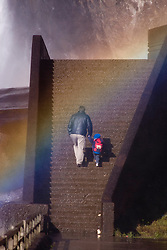 Pai segura a mao do filho e caminham na direcao do arco iris nas Cataratas de Montmorency/ Father holding his childs hand while they walk to a rainbow in Montmorency Falls