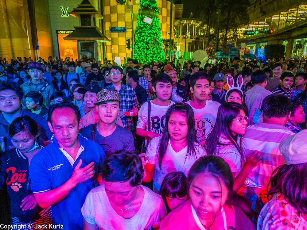 31 DECEMBER 2013 - BANGKOK, THAILAND: People enjoy one of the concerts at the Bangkok New Year's Eve party in Ratchaprasong Intersection. Hundreds of thousands of people pack into the Ratchaprasong Intersection in Bangkok for the city's annual New Year's Eve countdown. Many Thais go the Erawan Shrine and Wat Pathum Wanaram near the intersection to pray and make merit.     PHOTO BY JACK KURTZ