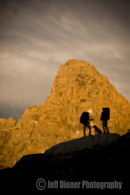 The Grand Teton looms behind two hikers in the high alpine of the Teton Range, Wyoming (de-focused).