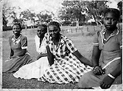 Four Nubian women sit on the green grass in the Laini Saba area of Kibera.  Laini Shaba area was an old shooting range for the King's African Rifles.   (circa 1950s)