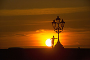 UNITED KINGDOM, London: 19 April 2018. Putney local Sophie Bowker, aged 27, stops to admire the sun on Putney Bridge as it sets on what has been the hottest April day in 70 years. Temperatures were recorded at 27.9C (82.2 F) with people told to stay out of direct sunlight and keep hydrated. Rick Findler / Story