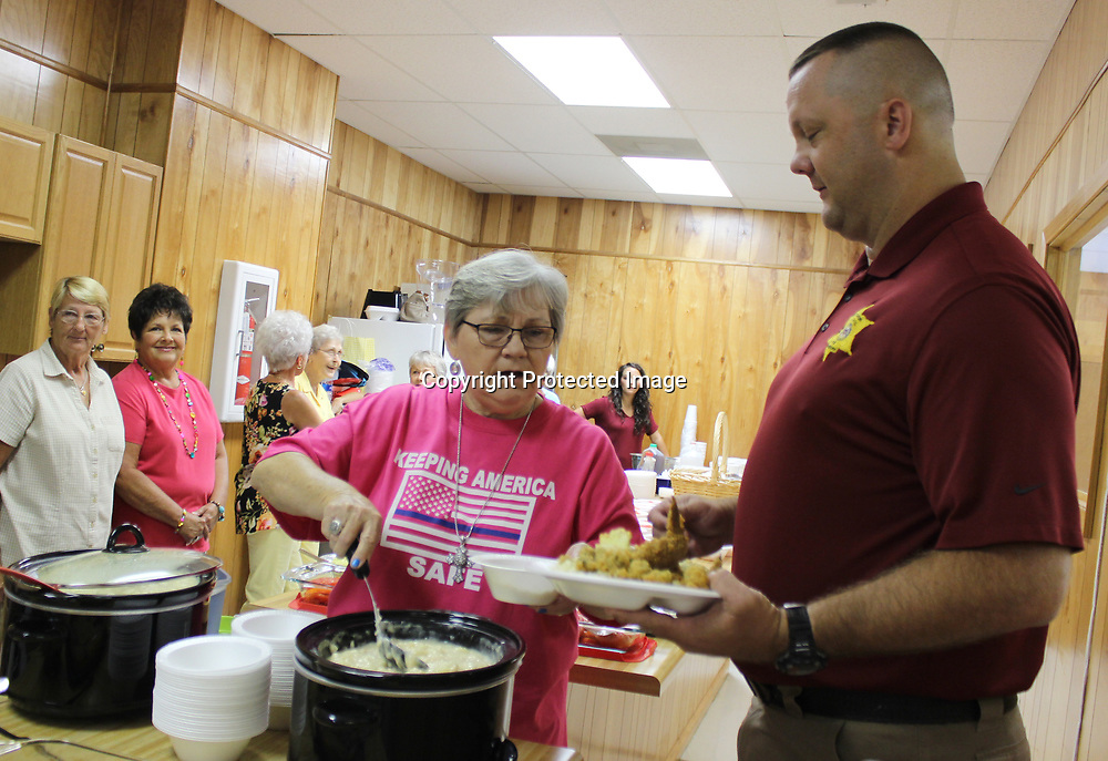 RAY VAN DUSEN/MONROECOUNTYJOURNAL.COM<br /> River Bend Baptist Church member Wanda Walker serves Monroe County Sheriff's Office Investigator Brandon Davis a bowl of chicken and dumplings during a luncheon the church hosted in appreciation of first responders.