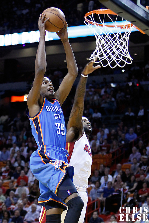 16 March 2011: Oklahoma City Thunder small forward Kevin Durant (35) dunks the ball past Miami Heat small forward LeBron James (6) during the Oklahoma City Thunder 96-85 victory over the Miami Heat at the AmericanAirlines Arena, Miami, Florida, USA.