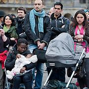Vrouwen Tegen Uitzetting (VTU) voert op 14 april 2012 een 'lig-actie' op de Dam.Tégen het op straat zetten van vluchtelingen, vóór fatsoenlijke opvang.VTU is een netwerk van Nederlandse en vluchtelingenvrouwen met en zonder verblijfsvergunning. VTU zet zich in voor een goed asielbeleid en aandacht voor de positie van vrouwelijke vluchtelingen.Het protest richt zich in de eerste plaats tegen het op straat zetten van vluchtelingen en pleit voor fatsoenlijke opvang. Maar er komt meer aan de orde. Diverse sprekers belichten of bezingen het wetsontwerp over 'gewortelde kinderen', het Kinderpardon, de schandalig hoge legeskosten en de slordige, haastige, asielprocedure.Om 15.00 u worden één voor één de namen van vluchtelingen  opgelezen die op straat zijn gezet, terwijl de aanwezigen op de Dam gaan liggen om te laten zien hoeveel asielzoekers op straat moeten leven.Sprekers zijn o.a. Vincent Bijloo cabaretier; Marieke Doorninck (Groen Links gem Amsterdam); Khadija Arib (2e K PvdA); Tofik Dibi (2e K GroenLinks)Stephanie Mbanzendore - Burundese en Myra..De vrouw met de groene sjaal is Khadija Arib 2e Kamer PvdA. Foto JOVIP/JOHN VAN IPEREN