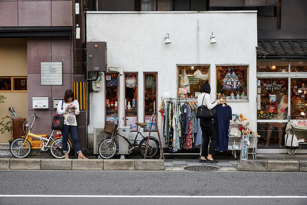 A woman checks her smart phone while another browses clothes outside a store in Gion.