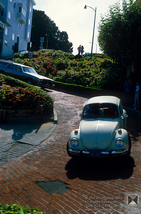 """Classic VW Bug turning one of the many curves of Lombard Street, """"the crookedest street in the U.S. Lombard Street is best known for the one way section on Russian Hill between Hyde and Leavenworth Streets, in which the roadway has eight sharp turns (or switchbacks) that have earned the street the distinction of being """"the crookedest [most winding] street in United States."""" San Francisco, California..Subject photograph(s) are copyright Edward McCain. All rights are reserved except those specifically granted by Edward McCain in writing prior to publication...McCain Photography.211 S 4th Avenue.Tucson, AZ 85701-2103.(520) 623-1998.mobile: (520) 990-0999.fax: (520) 623-1190.http://www.mccainphoto.com.edward@mccainphoto.com."""