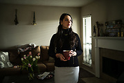 "BIRMINGHAM, AL – FEBRUARY 16, 2018: Anna Lewis, 25, stands in a sober living apartment where she is in recovery for alcohol addiction. <br /> <br /> As a teenager, Lewis first encountered opiates through pain medication that was prescribed to her after a car accident in high school. Oxycontin, the social drug of choice at the time, was so prevalent in her hometown of Pensacola, Fla., that experimentation was easy. ""I didn't even have to look for it. It was just there – at my work, or my friends had it,"" she said. ""I didn't realize I was addicted until I felt like I had the flu one day, and after using, I felt normal. That's when I knew I had a problem."" Within a year, Lewis had switched to shooting heroine, and even moved to Atlanta where the drug was cheaper and easier to find. It took an arrest for possession while shoplifting books at a Barnes & Noble to finally realize she was an addict. ""I'd spent all my money on dope,"" Lewis said. ""So those books were my friends. It's hard to have real friends when you're using. Dope is your priority. The people you're around are sick too, so no one is looking out for you. Everyone's focus is dope."" At age 19, Lewis finally kicked the heroine habit after checking herself into a detox program, but she soon turned to alcohol. ""It only took about a year for me to become an alcoholic – needing it on a daily basis,"" she said. Today, Lewis has been sober from alcohol for 3 months, but she says she's painfully aware of the money her mother and grandmother have spent on rehab, and has felt obligated to pay back what she can. ""My mom has always been there for me, and she still is,"" Lewis said. ""It's been life saving to know that I'm able to call her anytime, and there will be love on the other end of the line."" <br /> <br /> The addiction crisis that is killing tens of thousands of Americans every year is also creating a financial crisis for many families, compounding the anguish caused by a loved one'�"