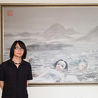 "VENICE, ITALY - JUNE 02:  Artist Jeang Heng  poses  in front of ""Gift from Ruth Handler"" a painting  part of the Exhibition Future Pass on June 2, 2011 in Venice, Italy. The Venice Art Biennale will run from June 4 to November 27, 2011."