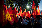 A supporter of the Greek communist party (KKE) walks along with a parade of flags in Athens, Greece. Image © Angelos Giotopoulos/Falcon Photo Agency