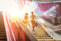 Businessman and businesswoman talking while walking down stairs with lens flare in background