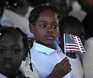 Grade school girl holding American Flag.