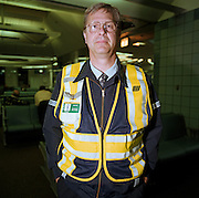 A United Airlines ramp agent stands in the terminal building of Chicago O'Hare airport before continuing his airside shift, dispatching and communicating with his operational airline colleagues. The man stands with hands in pockets wearing his company issue fluorescent safety jacket with reflective materials important on the ramp, in the company of dangerous vehicles and running aircraft engines. Ensuring the smooth arrival and departures of flights across America and the rest of the world, he is a key member of the airline at its O'Hare hub. Picture from the 'Plane Pictures' project, a celebration of aviation aesthetics and flying culture, 100 years after the Wright brothers first 12 seconds/120 feet powered flight at Kitty Hawk,1903. .