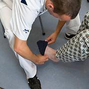Nederland Rotterdam  31-08-2009 20090831 Foto: David Rozing .Serie over zorgsector, Ikazia Ziekenhuis Rotterdam. Afdeling neurologie, stroke unit, Broeder trekt sokken aan bij oude man. De patient heeft een beroerte gehad en daardoor is oa zijn ( grove ) motoriek aangetast, deels verlamd geraakt.  Nurse puts on socks old patient, helping him. patient has suffered a stroke. .Na een ernstige beroerte wordt u opgenomen in een gespecialiseerde afdeling of een afdeling intensieve zorgen van het ziekenhuis. Na de eerste 24 uur is het nodig om een aangepast revalidatieprogramma te starten. dat kan bestaan in wisselhoudingen en passieve bewegingen van de verlamde lichaamshelft.  .  ..Foto: David Rozing   ....Holland, The Netherlands, dutch, Pays Bas, Europe, ronde doen, routine verpleegkundigen , verpleger, verplegers, verplegend, .,interactie patient verpleging, hulp, helpen,, nursing, aansterken, handeling, handelingen,Holland, The Netherlands, dutch, Pays Bas, Europe, menselijk contact ,   oud, oude, op leeftijd, revalidatie, revalideren, revalidation, nursing,steun, steunen, helpen met aan kleden aan te kleden.,ziektekosten,zorgverlener, zorgverleners,zorgverlening,oud ,ouderen, bejaard, bejaarde, bejaarden, op leeftijd zijn, oude van dagen, ouderenzorg, bejaardenzorg, verpleger, verplegers, verplegend