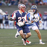 Kevin Buchanan #27 of the Boston Cannons keeps the ball away from Josh Hawkins #3 of the Charlotte Hounds during the game at Harvard Stadium on May 17, 2014 in Boston, Massachuttes. (Photo by Elan Kawesch)