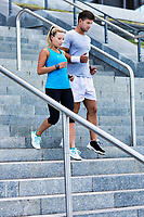 Young attractive couple exercising in stairs