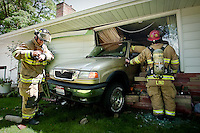 JEROME A. POLLOS/Press..Coeur d'Alene firefighters Tony Bajadali, left, and Lt. Joe Lind secure an accident scene where a woman with a learner's permit backed into her neighbor's home Tuesday at 17th Street and Foster Avenue in Coeur d'Alene. No one was injured in the accident.