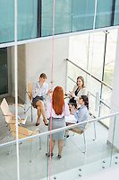 High angle view of businesswoman giving presentation to colleagues in office