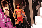 A woman is posing behind a stand selling bondage tape at the Erotica 2006 show in London, UK, on Friday, Nov. 17, 2006. Erotica is the world's largest adult lifestyle show. It attracts about 80,000 visitors every year with its over 150 retailer exhibitors, dazzling and decadent transvestite cabaret shows, fun foreplay seminars, beautiful lingerie collections, art and fetish demonstrations. **Italy Out**