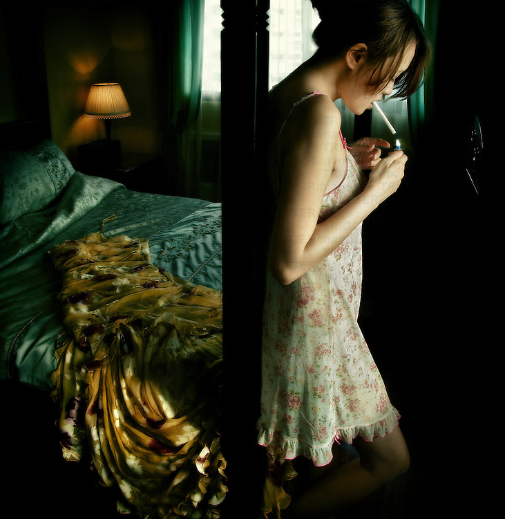 Young woman standing leaning against bed post in underwear lighting cigarette with silk dress on bed