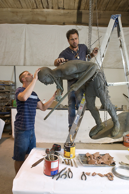 Forest Boone and his assistant, Michael Stephenson, begin restoration of a sculpted Native American statue constructed by famed Louisville sculptor Barney Bright Wednesday, June 6, 2012 at his studio in the Hope Worsted Mills warehouse. (Photo by Brian Bohannon)