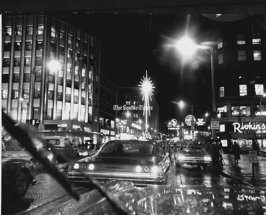 Looking north on Fourth Avenue in downtown Seattle, lights from automobiles glistened and winked as Christmas shoppers hurried on their appointed rounds. Street lights blinked and the emblem of a department store shone like a huge decoration. This photo was taken from the window of an automobile.<br /> <br /> Josef Scaylea / The Seattle Times, 1967
