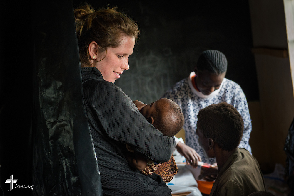 Nurse Casey Peters of Dover, N.H, cradles a young patient during the Mercy Medical Team clinic Wednesday, June 11, 2014, at the Luanda Doho Primary School in Kakmega County, Kenya. LCMS Communications/Erik M. Lunsford