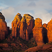 Coffee Pot Rock, on the right, is one of Sedona, Arizona's famous red-rock landmarks. The area is surrounded by red rock towers that light up with the golden light of sunset.