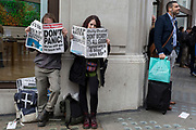 Environmental activists read copies of a fake newspaper with fictional headlines about the effects of global Climate Change during an occupation of Oxford Circus in central London, part of a two-week prolonged worldwide protest by members of Extinction Rebellion, on 18th October 2019, in London, England.